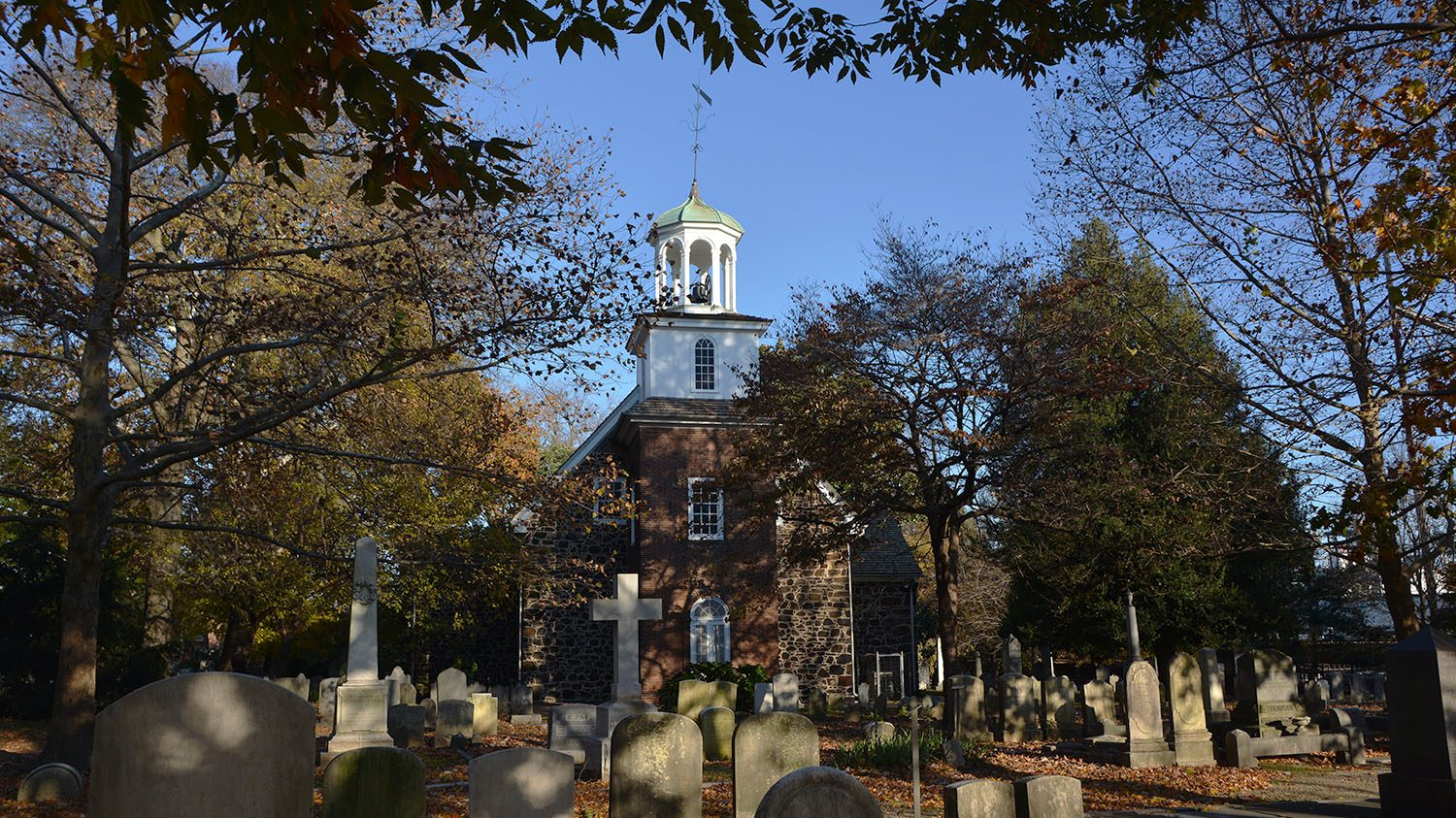 A photo of Old Swedes Church and graveyard in the fall.